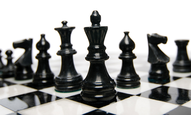 Close-up of black and white marble chess pieces on a chess board.