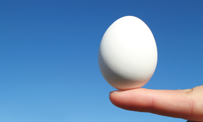 white egg and the forefinger in the blue sky background