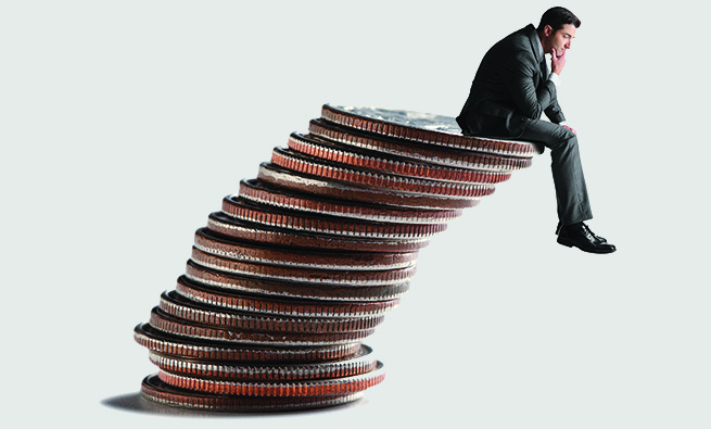 A businessman sitting on a stack of coins about to tumble over.