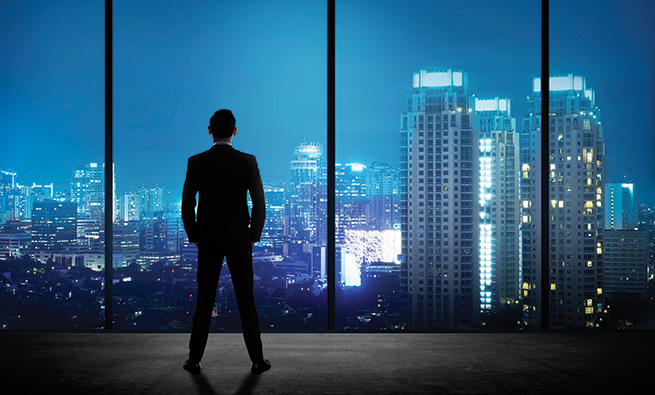 Man standing in his office looking at the city at night. Business success concept
