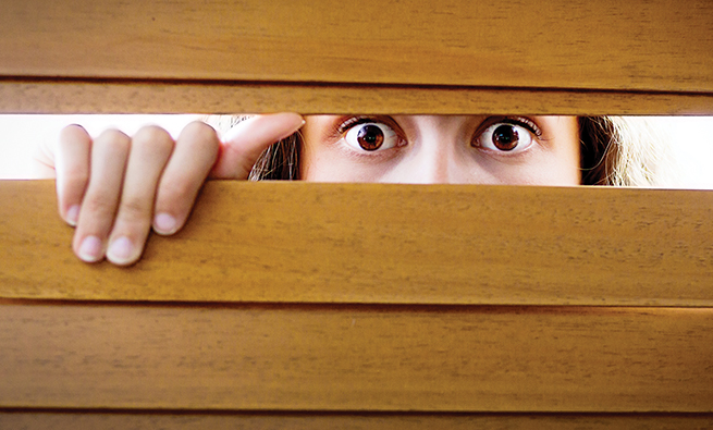 A  young woman looks, wide eyed and worried, through the slats of a wooden Venetian blind. She could be having home security issues, witnessing a crime, or simply be extremely nervous. Copy space on the slats of the blind.