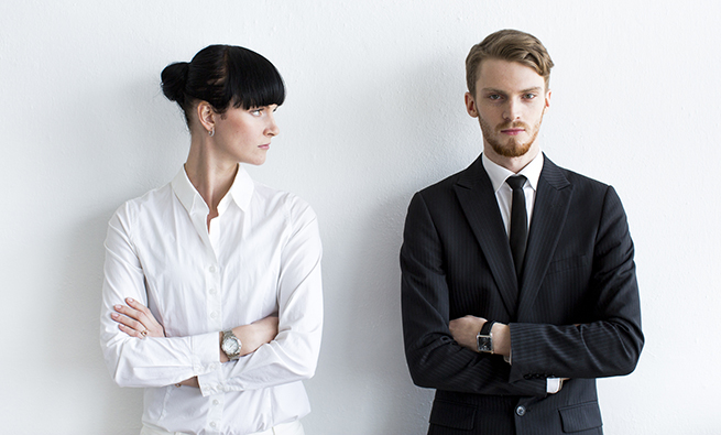 Two young CEOs are standing at a white wall in their office arms crossed. The woman is looking discontent at the man while he's looking straight at camera, confident and satisfied. The woman is wearing white, has black hair while the man is wearing black suit and has bright hair. Image contains plenty of copy space.