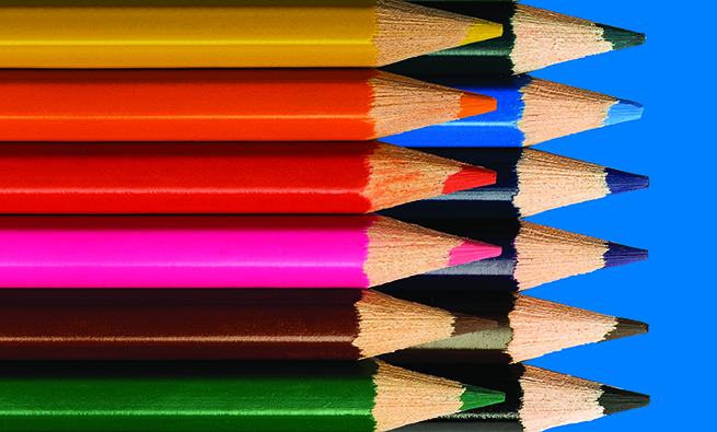 Colored pencils in a row on green background