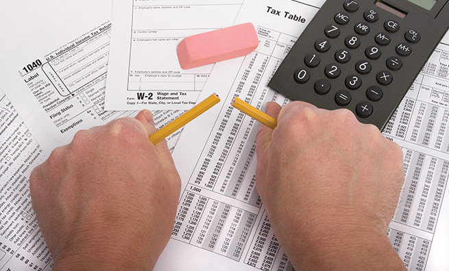 Hands breaking pencil in frustration over tax forms