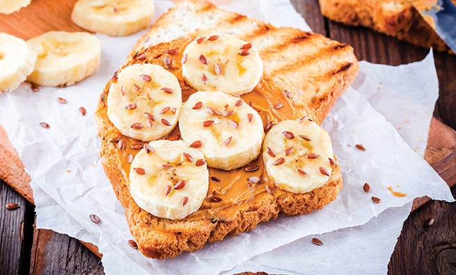 Peanut butter toast with banana slices and flax seeds on wooden background